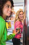 Woman giving a food can to her friend from a refrigerator Stock Photo - Premium Royalty-Free, Artist: Photocuisine, Code: 6108-05862514