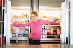 Portrait of a woman standing in front of a refrigerator Stock Photo - Premium Royalty-Free, Artist: Blend Images, Code: 6108-05862522