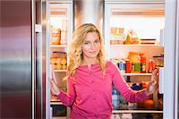 fridge - Portrait of a woman standing in front of a refrigerator Stock Photo - Premium Royalty-Freenull, Code: 6108-05862549