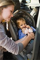 Woman fastening her son on a baby seat in a car Stock Photo - Premium Royalty-Freenull, Code: 6108-05862791