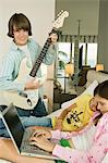 Boy playing a guitar and girl working on a laptop Stock Photo - Premium Royalty-Free, Artist: AWL Images, Code: 6108-05862984