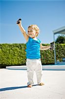 Baby boy holding a remote controlled car and smiling Stock Photo - Premium Royalty-Freenull, Code: 6108-05863164