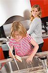 Girl washing glasses in the kitchen Stock Photo - Premium Royalty-Free, Artist: Raymond Forbes, Code: 6108-05863374