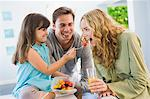 Girl feeding fruit salad to her mother Stock Photo - Premium Royalty-Freenull, Code: 6108-05863452
