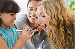 Girl feeding fruit salad to her mother Stock Photo - Premium Royalty-Freenull, Code: 6108-05863456