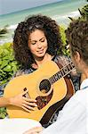 Woman playing a guitar in front of a man Stock Photo - Premium Royalty-Freenull, Code: 6108-05863649
