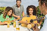 Friends enjoying beer and music on vacations Stock Photo - Premium Royalty-Free, Artist: R. Ian Lloyd, Code: 6108-05863651