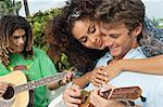 Woman embracing a man playing ukulele Stock Photo - Premium Royalty-Freenull, Code: 6108-05863656