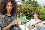 Woman with her friends playing musical instruments Stock Photo - Premium Royalty-Free, Artist: Blend Images, Code: 6108-05863663
