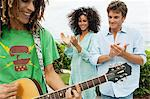 Man playing a guitar and his friends applauding him Stock Photo - Premium Royalty-Free, Artist: R. Ian Lloyd, Code: 6108-05863665