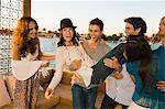 Man carrying a woman with his friends beside him Stock Photo - Premium Royalty-Free, Artist: AWL Images, Code: 6108-05863710