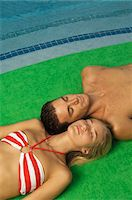 Couple sunbathing at the poolside Stock Photo - Premium Royalty-Freenull, Code: 6108-05863740