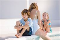 Woman with her two children sitting at the poolside Stock Photo - Premium Royalty-Freenull, Code: 6108-05863817