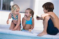 Two girls and a boy eating chocolate donuts at the poolside Stock Photo - Premium Royalty-Freenull, Code: 6108-05863844