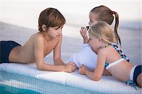 Two girls and a boy at the poolside Stock Photo - Premium Royalty-Freenull, Code: 6108-05863845