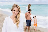 Woman smiling with her family in the background Stock Photo - Premium Royalty-Freenull, Code: 6108-05864014