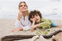 Boy lying with his mother on the beach Stock Photo - Premium Royalty-Freenull, Code: 6108-05864057
