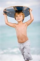 Boy holding a body board over his head Stock Photo - Premium Royalty-Freenull, Code: 6108-05864071