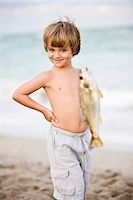 Boy holding a fish on the beach Stock Photo - Premium Royalty-Freenull, Code: 6108-05864116