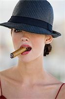 Fashion model smoking a cigar Stock Photo - Premium Royalty-Freenull, Code: 6108-05864309