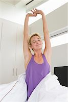 Woman stretching her arms on the bed at morning Stock Photo - Premium Royalty-Freenull, Code: 6108-05864384