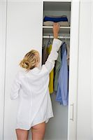 Woman selecting clothes in a wardrobe Stock Photo - Premium Royalty-Freenull, Code: 6108-05864442
