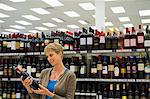 Woman reading a label of a wine bottle Stock Photo - Premium Royalty-Free, Artist: Cultura RM, Code: 6108-05864538