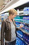 Woman buying water bottle in a store Stock Photo - Premium Royalty-Free, Artist: Cultura RM, Code: 6108-05864551