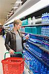 Woman buying water bottle in a store Stock Photo - Premium Royalty-Freenull, Code: 6108-05864556