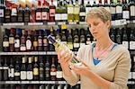 Woman reading a label of a wine bottle Stock Photo - Premium Royalty-Free, Artist: Ikon Images, Code: 6108-05864562