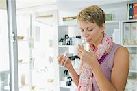 smelly - Woman smelling perfume in a store Stock Photo - Premium Royalty-Freenull, Code: 6108-05864737