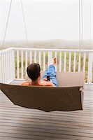 Man using a mobile phone on a porch swing Stock Photo - Premium Royalty-Freenull, Code: 6108-05865021