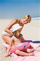 Woman applying suntan lotion on her daughter on the beach Stock Photo - Premium Royalty-Freenull, Code: 6108-05865144