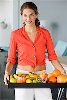 Portrait of a woman holding fruits Stock Photo - Premium Royalty-Freenull, Code: 6108-05865458