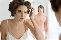 Woman using curlers with her boyfriend in the background Stock Photo - Premium Royalty-Freenull, Code: 6108-05865499