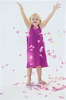 Girl tossing flower petals and smiling Stock Photo - Premium Royalty-Freenull, Code: 6108-05865567