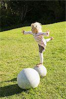 Girl balancing herself on a round stone Stock Photo - Premium Royalty-Freenull, Code: 6108-05865583