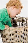 Baby boy looking into a wicker basket Stock Photo - Premium Royalty-Free, Artist: Emanuele Ciccomartino, Code: 6108-05865645