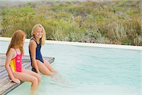 Two girls sitting on a platform at an infinity pool Stock Photo - Premium Royalty-Freenull, Code: 6108-05865911