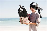 Boy in pirate costume playing with a toy boat Stock Photo - Premium Royalty-Freenull, Code: 6108-05865967