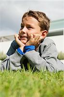 Boy lying on grass and day dreaming Stock Photo - Premium Royalty-Freenull, Code: 6108-05866403