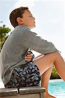 Boy day dreaming near a swimming pool Stock Photo - Premium Royalty-Freenull, Code: 6108-05866456