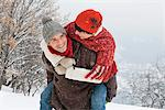 Young man giving his girlfriend piggyback in snow Stock Photo - Premium Royalty-Free, Artist: Robert Harding Images, Code: 6108-05867013