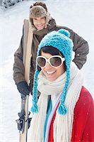 Young woman in winter clothes smiling at camera, man holding skis in background Stock Photo - Premium Royalty-Freenull, Code: 6108-05867016