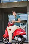 Portrait of young man sitting on a scooter and text messaging Stock Photo - Premium Royalty-Free, Artist: Glowimages               , Code: 6108-05869882
