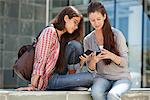 Two young female friends reading messages Stock Photo - Premium Royalty-Freenull, Code: 6108-05869905