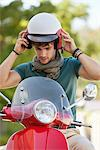 Young man wearing helmet sitting on scooter Stock Photo - Premium Royalty-Free, Artist: Glowimages               , Code: 6108-05869915