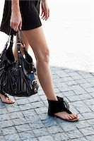 Low section view of a young woman wearing modern flat sandal and walking Stock Photo - Premium Royalty-Freenull, Code: 6108-05870007