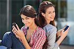 Portrait of two young women sitting back to back and using mobile phones Stock Photo - Premium Royalty-Freenull, Code: 6108-05870079