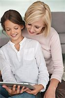 Woman assisting her daughter in using a digital tablet Stock Photo - Premium Royalty-Freenull, Code: 6108-05870090